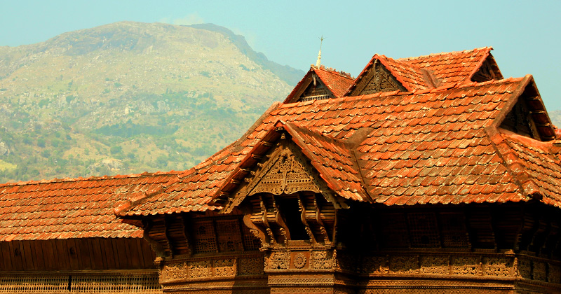 veduta del tetto con finestre scolpite su sfondo monte e cielo azzurro