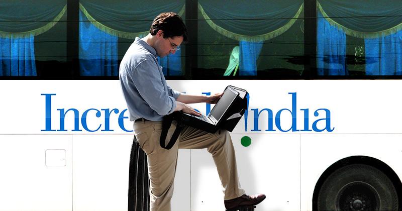 Un giovane uomo lavora a un portatile mentre un autobus indiano passa dietro di lui