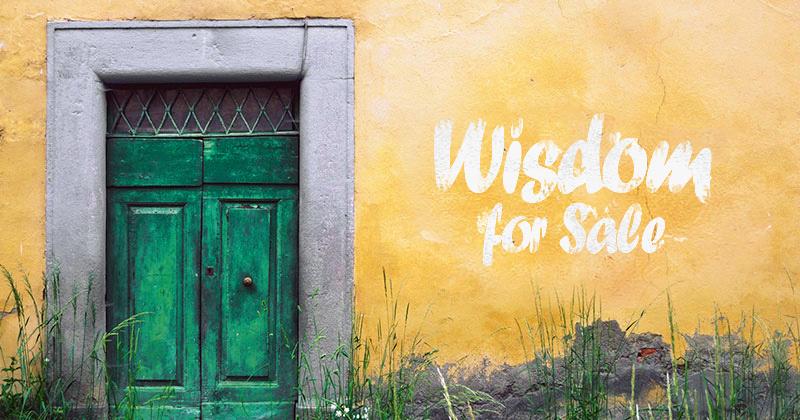 un muro di casa giallo sbiadito con una porta verde. Sul murp la scritta bianca Wisdom for sale